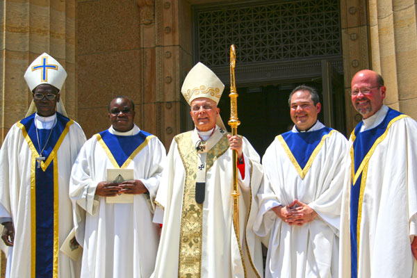 After the ordination Mass, the new priests pose for pictures on the steps of the Cathedral. Pictures (l-r) are: Archbishop Gregory Kpiebaya, the archbishop emeritus of Tamale in Ghana, Father Paul Kala, Cardinal Francis George, O.M.I., Father Stephen Thompson and Monsignor Carl Kemme.